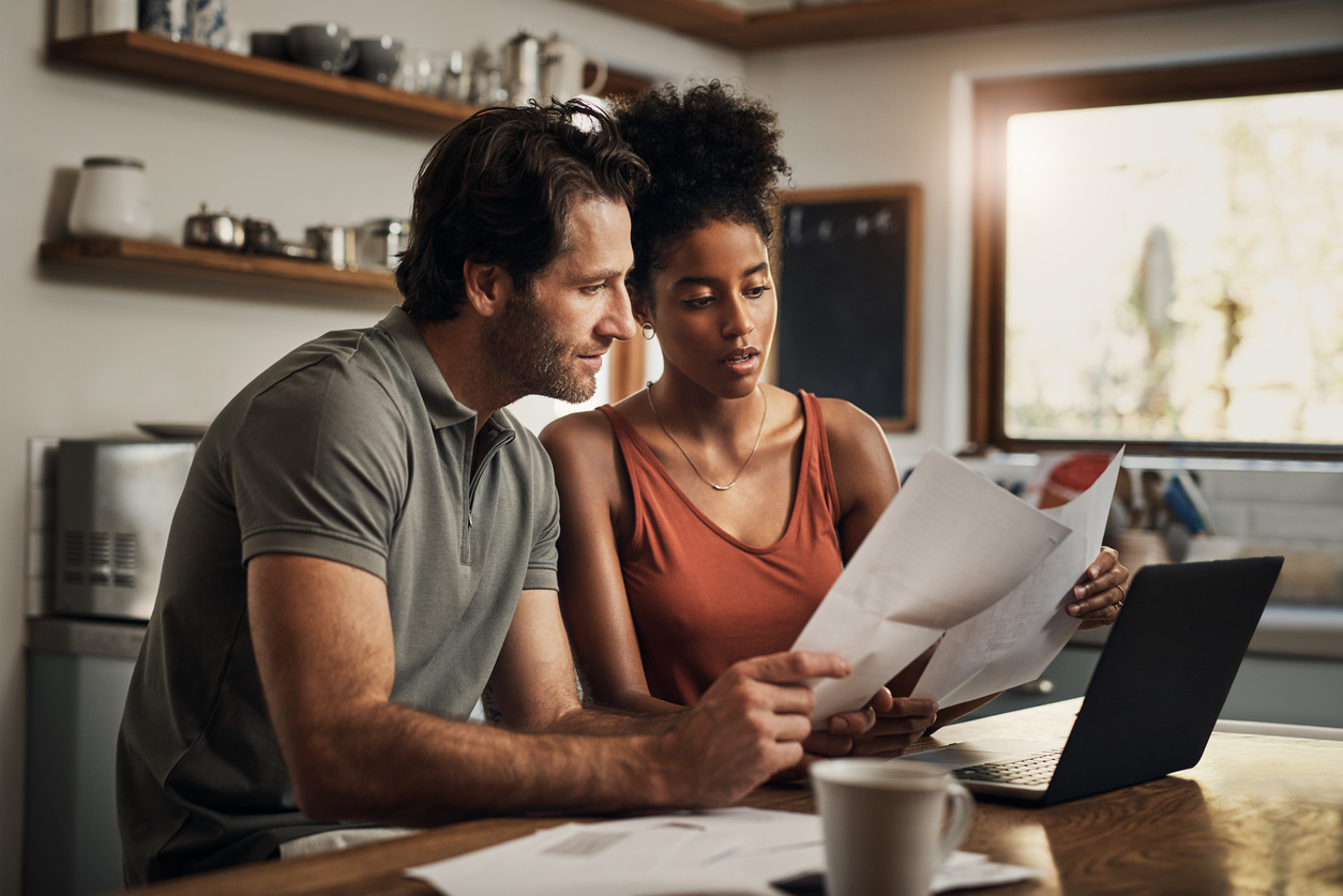 Couple looking over paperwork at home